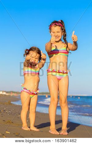 Little kids enjoy the summer holidays and swiming in sea water at the beach.