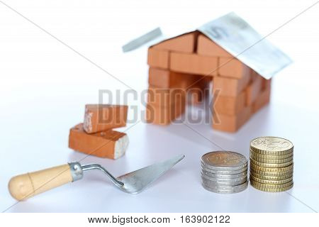 symbolic house with red bricks and money