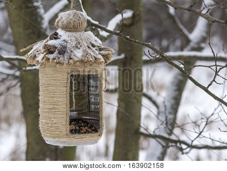 Vintage bird feeders. Handmade. Bird feeder covered with snow. Small depth of field.