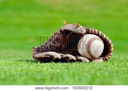 Baseball glove and baseball on the field