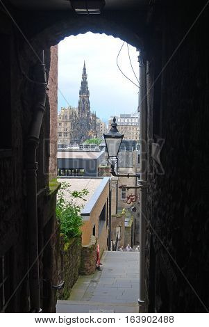 Edinburgh, United Kingdom - June 14, 2014. View down a narrow wynd in Edinburgh, with vista of Scott Monument, historic buildings, street lamp and people.