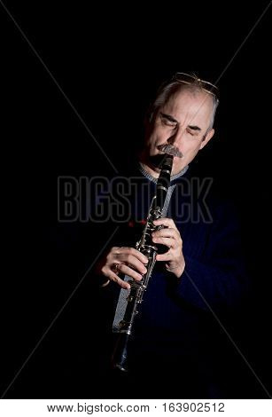 A mature man playing the clarinet jazz .