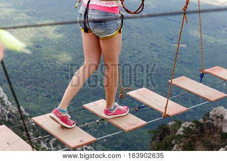 Young girl walking on rope ladder in mountains in summer