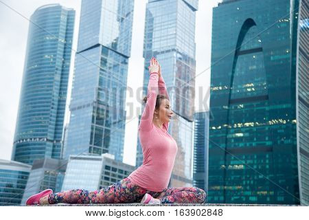Young woman practicing yoga, sitting in Single Pigeon, One Legged King Pigeon exercise, Eka Pada Raja Kapotasana pose, working out wearing pink sportswear, outdoor full length, city background