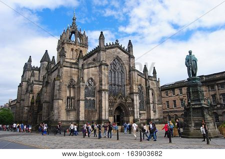 Edinburgh, United Kingdom - June 14, 2014. St Giles Cathedral in Edinburgh, with statue of the 5th Duke of Buccleuch on Royal Mile, surrounding buildings and people.