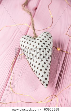 heart with polka dots on a pink wooden background