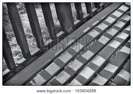 Detail of frosty garden bench in autumn park landscape