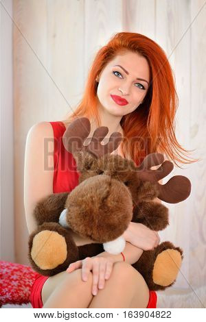 Beautiful Red-haired Woman With A Toy Elk. The Concept Of Christmas.