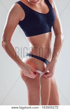 Woman measuring perfect shape of beautiful hips on grey background. Healthy lifestyles concept