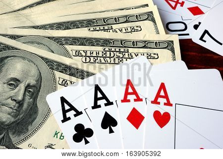 Four aces and dollars on a wooden sureface.