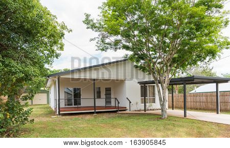 New contemporary style home with carport trees and garden