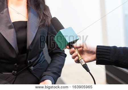 The men's hands with the microphone. Media interview. The reporter interviews the woman.
