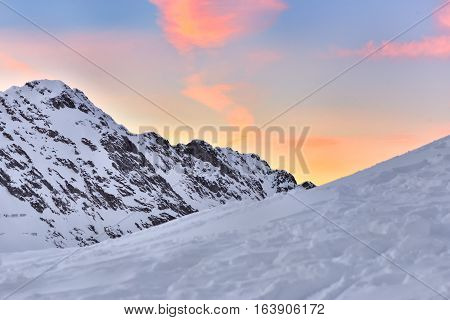 Beautiful view of mountain peak with sunset light on top against colored cloudy sky