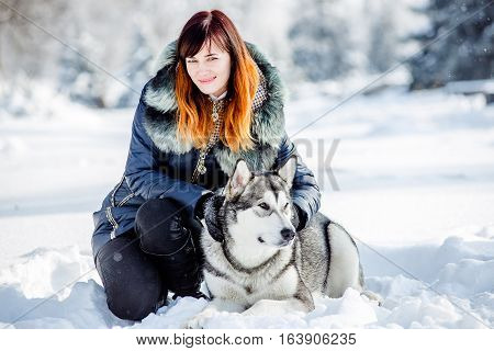 Walking with a dog in the park in winter. Winter activities with the dog. Cheerful brunette walking in the park with his dog in the winter. Girl sits near a dog in the winter in the snow