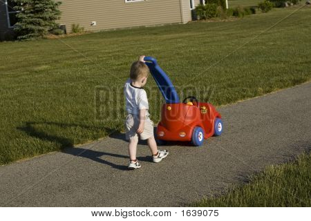 Young Boy Pushing A Toy
