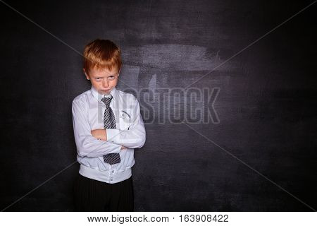Redhead schoolboy stands near a school board frowning. Free space. Black background. School concept