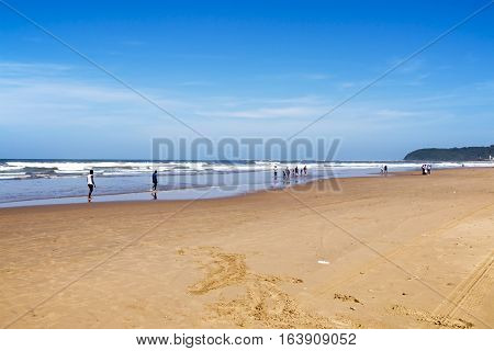 People On Early Morning Beach Against Ocean Skyline