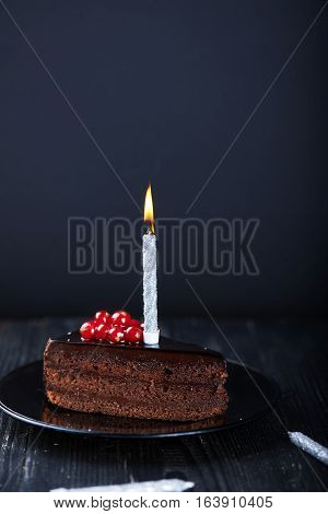 A slice of chocolate cake with redcurrant and a single lit candle on a dark background. Vertical shot