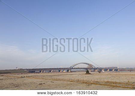 bridge over motorway A2 and wintry meadows in floodplains of river Lek near Vianen in the netherlands