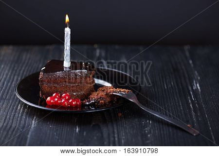 A slice of chocolate cake with redcurrant, fork and a single lit candle on a dark background. Dark photo.