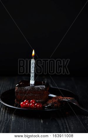 A slice of chocolate cake with redcurrant, fork and a single lit candle on a dark background. Dark photo. Low key.