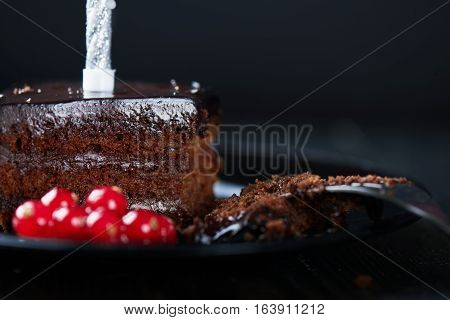 Close view at slice of chocolate cake with redcurrant, fork and a single candle on a dark background. Dark photo.