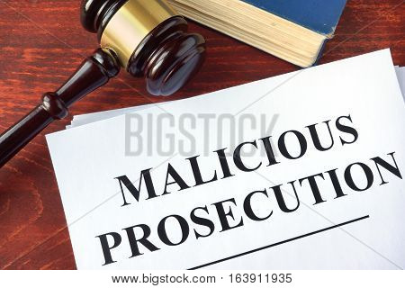Malicious prosecution, documents and gavel on a table.