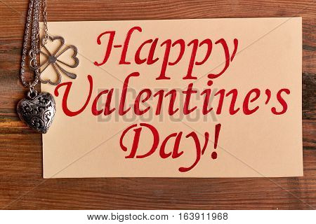Heart-shaped pendant and greeting card. Happy Valentine's Day inscription. Jewelry as present for sweetheart.