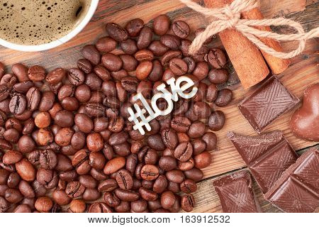 Hashtag love inscription near candies. Cinnamon sticks and coffee beans. Aromatic start of the day.