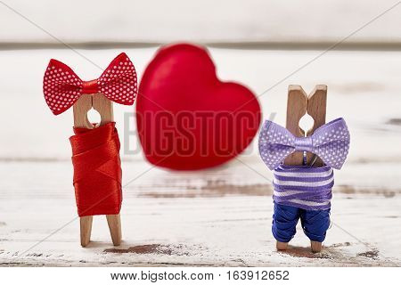 Red heart and clothespin couple. Heart on wooden background. Couple personalization by clothespins.