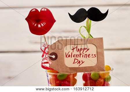 Valentine's Day tag and candies. Label near mustache and lips. Shopping and entertainment.