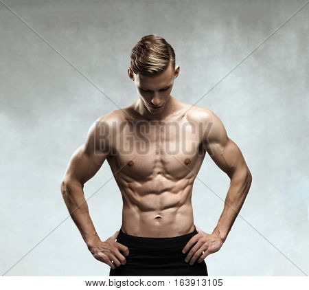 Strong Athletic Man Fitness Model Torso showing six pack abs. isolated on gray background with clipping path.