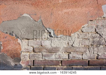 Old destroyed plaster at a brick wall. Grunge cement with a shabby paint background.