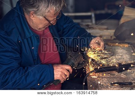 Mature male worker grinding piece of metal with grinder tool in workshop without protective equipment