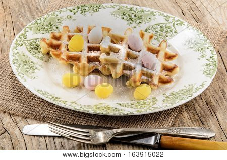 easter breakfast waffles with powdered sugar and small sugar eggs on a plate