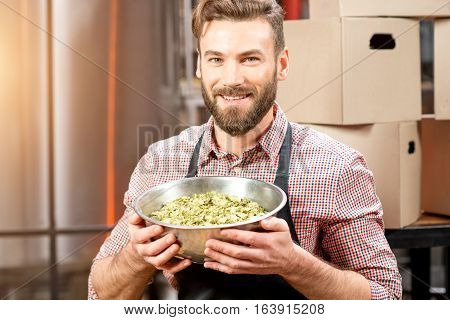 Portrait of a brewer with green hops dressed in apron and checkered shirt at the manufacturing