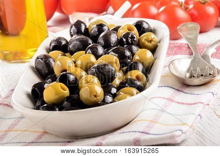 green and black olives in a bowl tomatoes olive oil fork and spoon in the background
