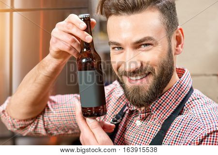 Portrait of a happy brewer holding a bottle with empty lable to copy paste at the manufacturing