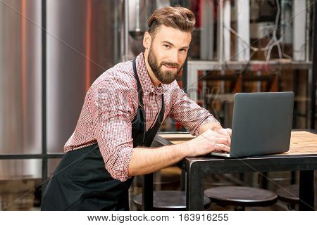 Portrait of a handsome brewer in apron and checkered shirt working with laptop at the manufacturing
