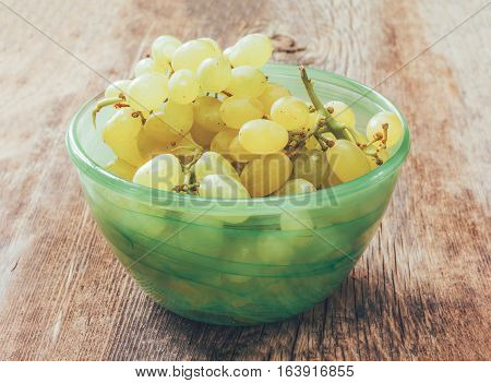 white grapes in a green bowl on old rustic wooden Board cracked. close up tinted photo