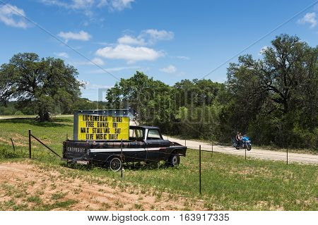 Luckenbach Texas USA - June 8 2014: Couple in a motorbike passing by a truck with a sign for a music event in Luckenback Texas.