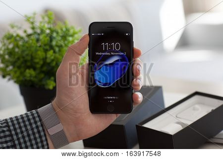 Alushta Russia - November 2 2016: Man hand holding iPhone 7 Jet Black with IOS 10 in the screen. iPhone 7 was created and developed by the Apple inc.