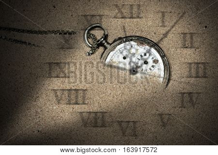 Broken pocket watch with shadows of clock hands and roman numbers partially buried in the sand