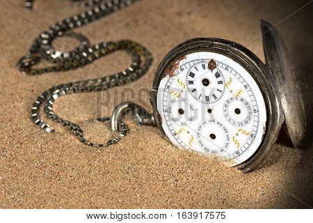 Old and broken pocket watch with chain and without clock hands partially buried in the sand