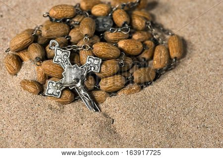 Detail of a silver crucifix and a rosary with wooden beads partially buried in the sand
