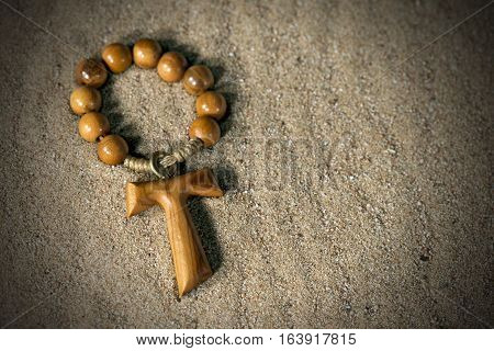 Tau wooden cross in the shape of the letter t (religious symbol of St. Francis of Assisi) with rosary bead over the sand