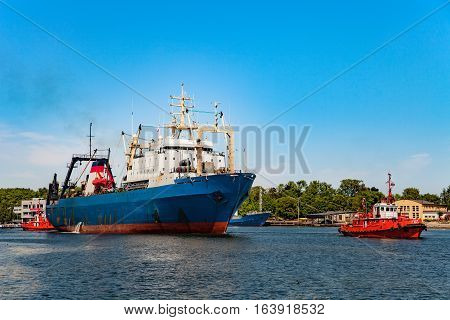 Tugboat towing fishing ship in port of Gdansk Poland.