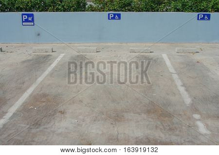 Empty parking space for cripple. Foreign text on blue signs is meaning