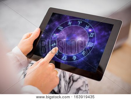 Woman reading horoscopes and predictions  on tablet computer