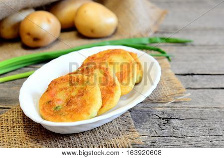Roasted vegetable cutlets. Potato cutlets with vegetables and spices on plate and on wooden table. Raw potatoes, fresh green onions. Vintage style. Closeup. Tasty vegetarian dish